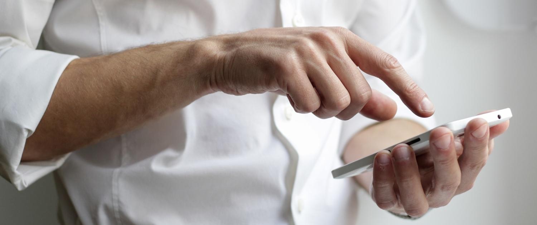 Person tippt etwas auf seinem weisen Smartphone.