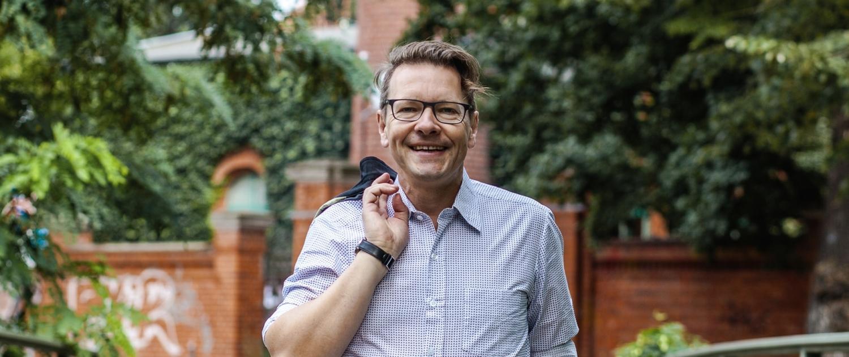 Holger Langer, lächelt mit der Jacke über der rechte Schulter haltend.